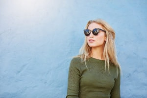 Woman in olive top wearing sunglasses